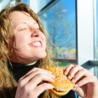 Stock Photo: Very happy woman is eating cheeseburger