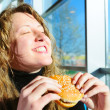 Very happy woman is eating cheeseburger — Stock Photo