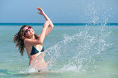 Funny woman splasing in the sea — Stock Photo