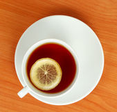 Tea cup with lemon on wooden table from above — Stock Photo