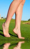 Beautiful female legs on grass near lake — Stock Photo