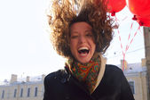 Laughing woman with red balloons on spring city — Stock Photo