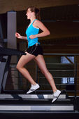 Beautiful woman is running on the treadmill — Stock Photo
