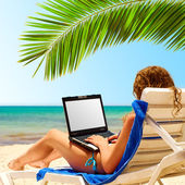 Surfing on the beach. Laptop display is cut wi — Stockfoto