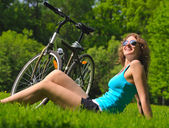Sitting woman and bike — Stock Photo