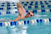 男は、屋内プールでクロール ストロークを使用して泳ぐ — ストック写真