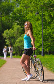 Woman with bicycle in park — Стоковое фото