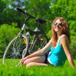 Sitting woman near her bike in park — Stock Photo