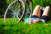 Woman is lying near her bicycle — Стоковое фото
