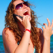 Cheerful woman is talking phone near sea — Stock Photo #3413606