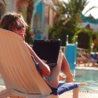Woman in tropical hotel with laptop — ストック写真