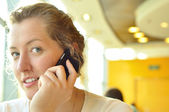 Young woman is talking phone and looking at camera — Stock Photo