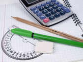 Protractor with pen and pencil on the workbook page — Stock Photo
