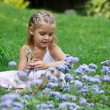 A little girl with flowers — Stock Photo