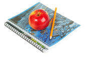 Red apple on spiral notebook — Stock Photo