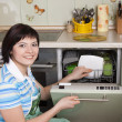 Foto Stock: Brunette woman cleaning kitchen