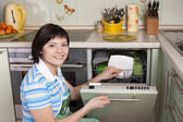 Bruneta žena úklid kuchyně — Stock fotografie