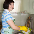 Stock Photo: Womwashing dishes in kitchen