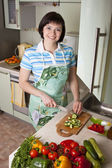 Woman cutting vegetables in kitchen — Stock Photo