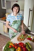 Legumes de corte de mulher na cozinha — Foto Stock