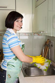 Woman washing dishes in kitchen — Stock Photo