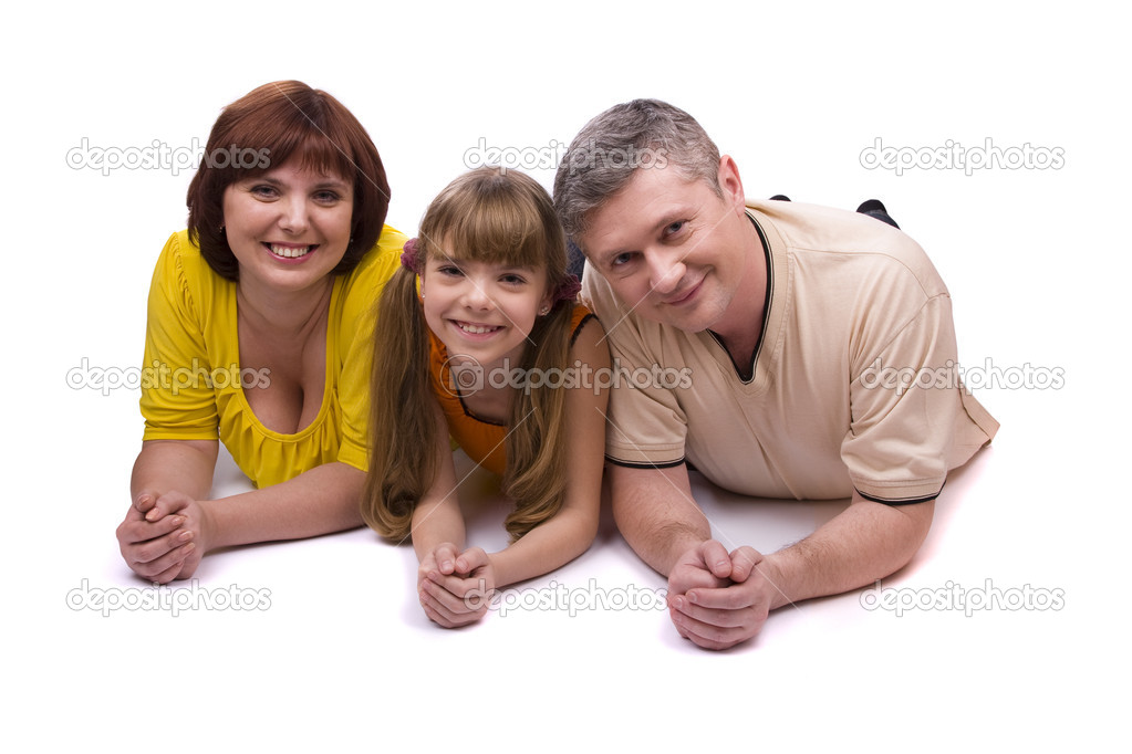 Happy family. Mother, father and little daughter are smiling . Woman, man and girl are lying on the floor and posing happily on white background. — Stock Photo #2841770
