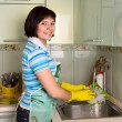 Woman washing dishes in kitchen — Stock fotografie