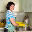 Foto Stock: Womwashing dishes in kitchen