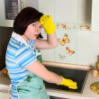 Smiling woman cleaning cooker — Stock Photo