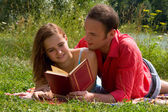 Couple reading and relaxing at the — Stock Photo