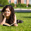 Foto Stock: Student studying on grass