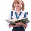 Schoolgirl is sitting on the stack of book and reading. — Stock Photo