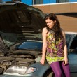Young blond woman with her broken car. — Lizenzfreies Foto