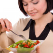 Foto Stock: Woman holding plate with salad and eating.