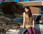 Młoda blond kobieta z jej uszkodzonego samochodu. — Zdjęcie stockowe