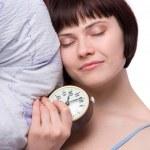 睡眼惺忪的女子是睡觉和持有闹钟 — 图库照片