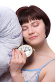 Sleepy woman is sleeping and holding alarm clock — Stock Photo