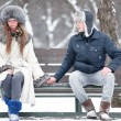 Young couple sitting on a bench — Stockfoto