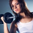 Young woman with dumbbell - Stock Photo