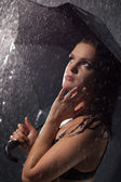 Young woman with umbrella under the rain — Stock Photo