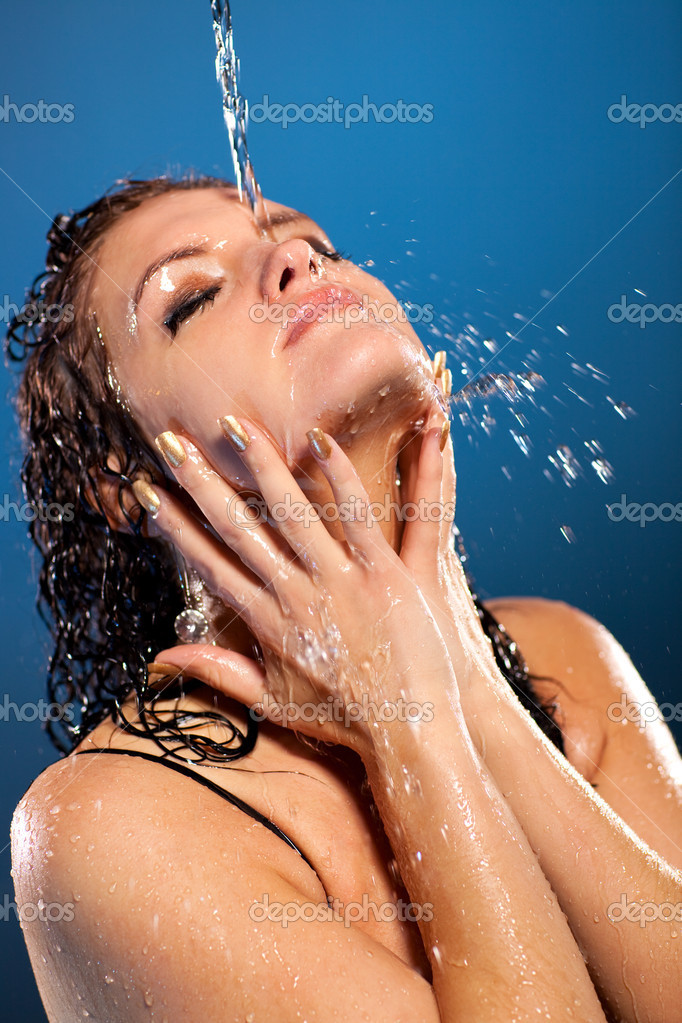 Water flowing on woman face. On blue background. — Stock Photo #3071715