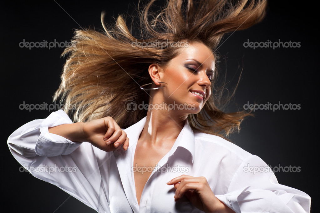 Woman with fluttering hair. On dark background. — Stock Photo #3071719