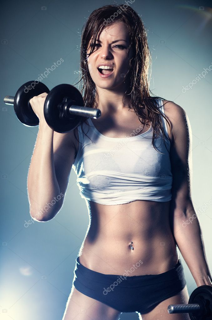 Young strong sexy woman with dumbbells. With flash effect. — Stok fotoğraf #3071818