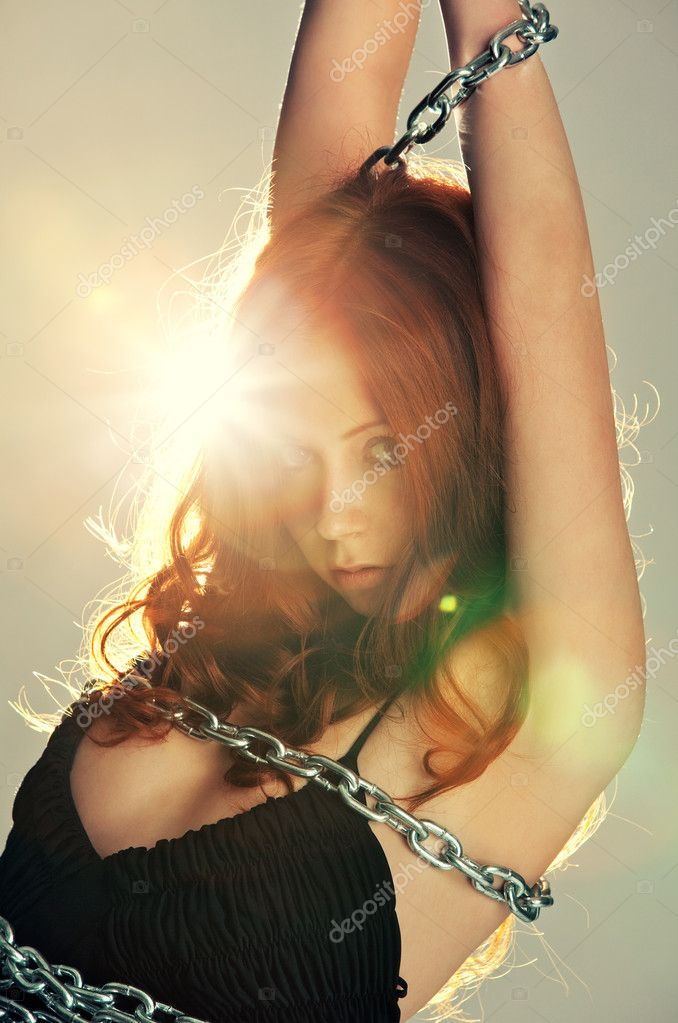 Young woman with chain portrait. Bright flash on background. — Stock Photo #3071846