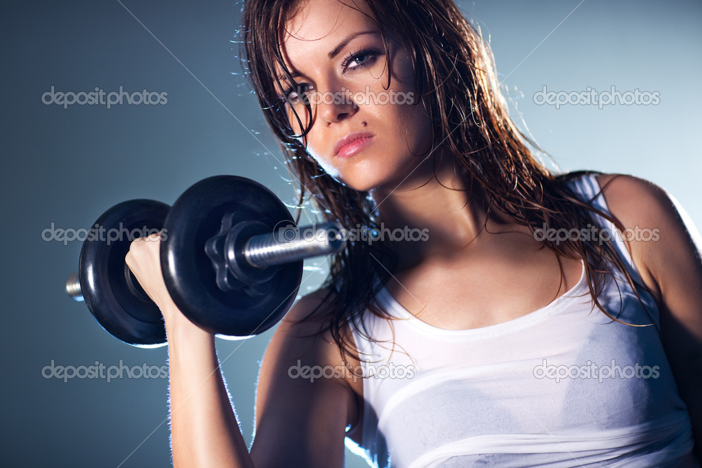 Young strong sexy woman with dumbbell. Camera angle view.  Stock Photo #3071883