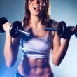 Young woman with dumbbells - Stock Photo