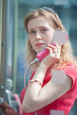 Young casual woman in call box — Stock Photo