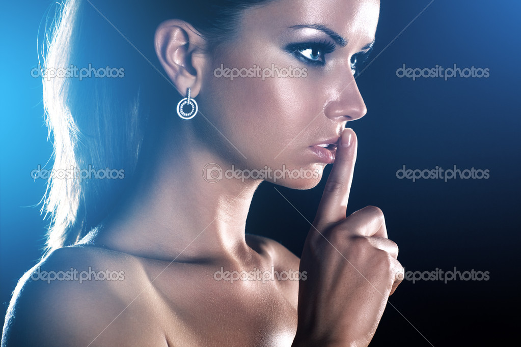 Young woman showing quiet handsign. On dark background. — Stock Photo #3728053