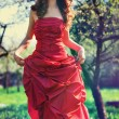 Young woman in red dress in garden — Stock Photo