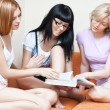 Three young women reading book — Foto Stock